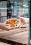 hands holding takeout salad